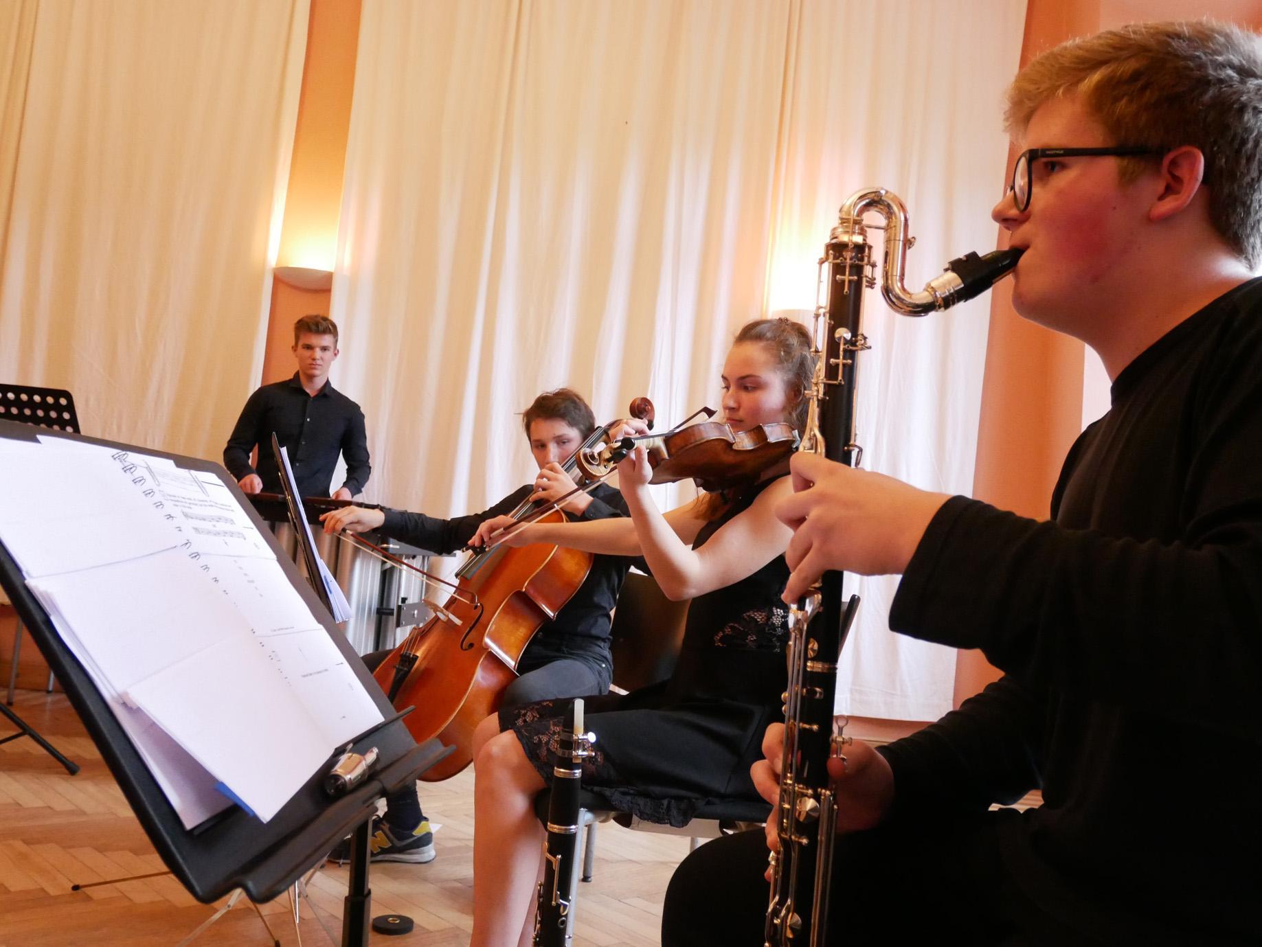 Junge Musikerinnen an Klarinette, Geige, Cello und Schlagwerk