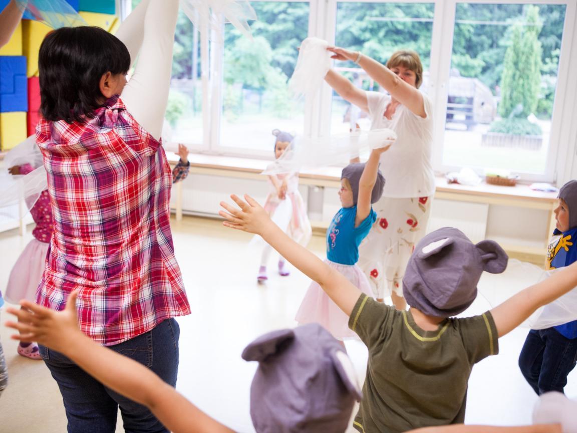 Eine Gruppe Erwachsene und Kinder tanzen mit Tüchern